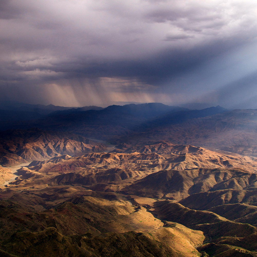 Hills with sunbeam and dark storm clouds in distance