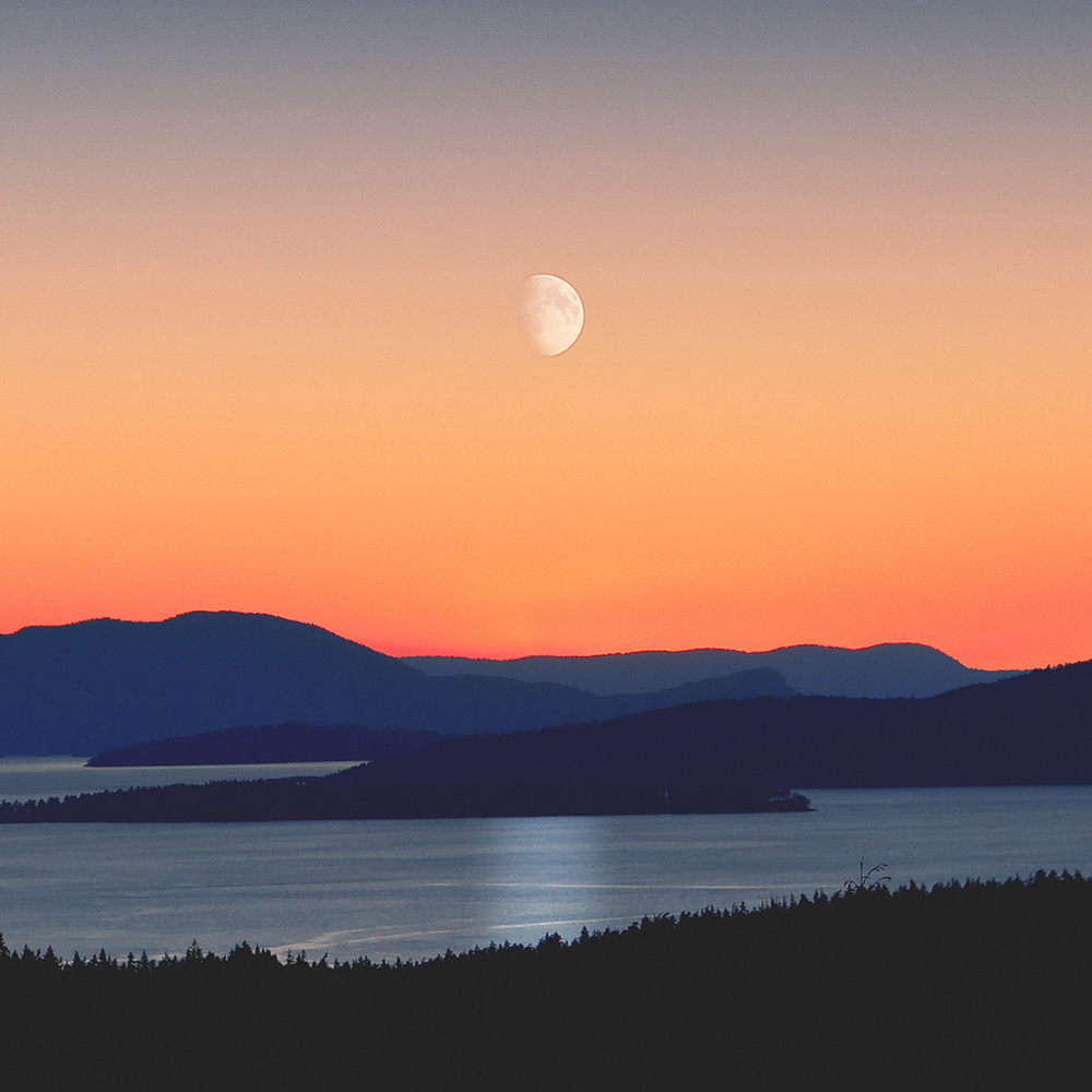 looking out across a lake and mountains with the moon visible at sunset.