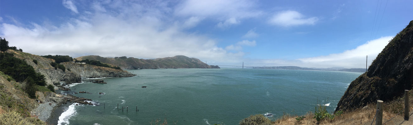 Panoramic view of Bay with hills and Golden Gate Bridge in the distance