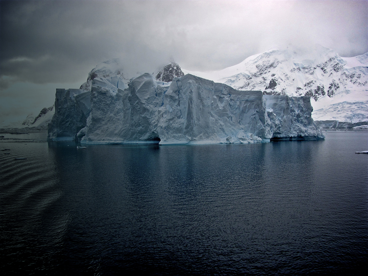 Iceberg with calm water and mountains