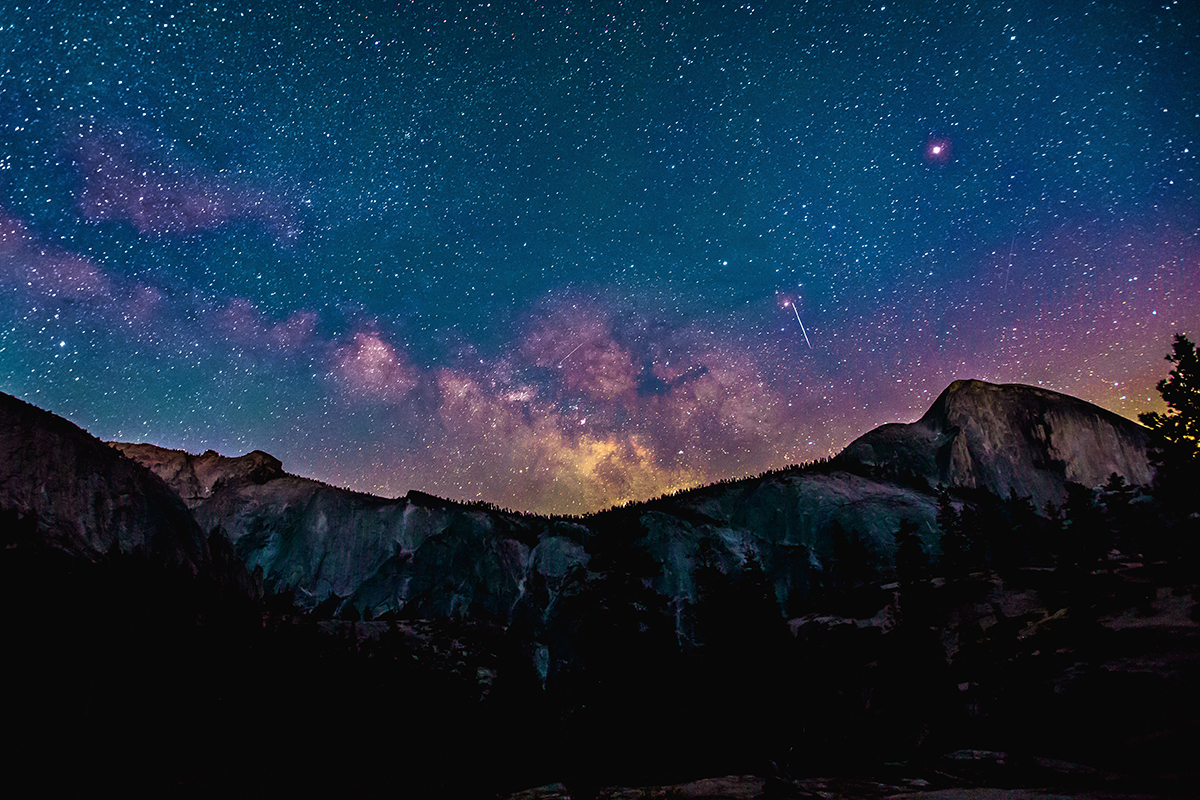 Mountains at night with stars and galaxy