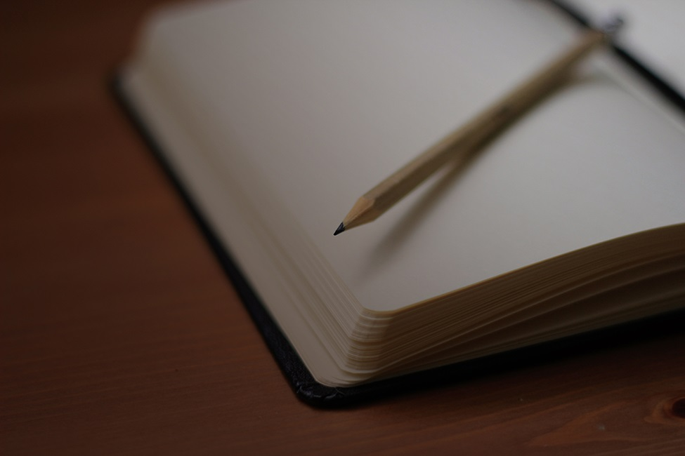 Blank notebook with sharpened pencil