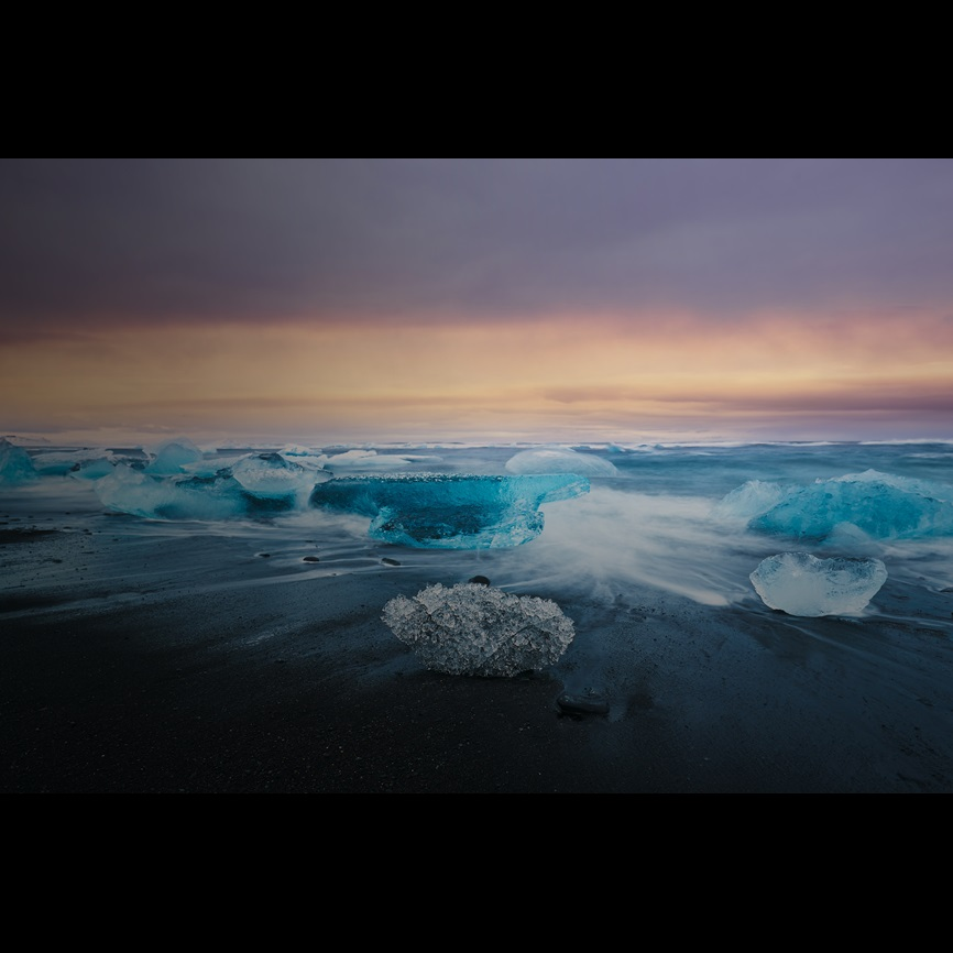 Long exposure of ice on beach at sunset