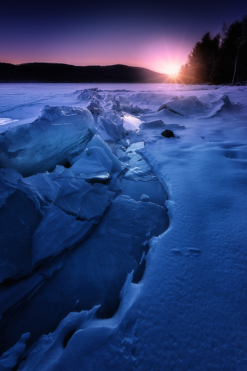 Sunrising over ice and snow covered stream