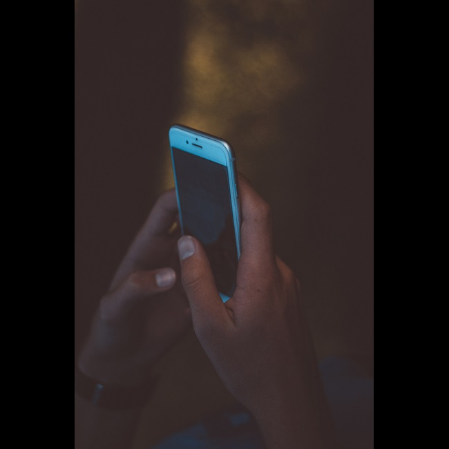 Dark image with person using phone and dark screen