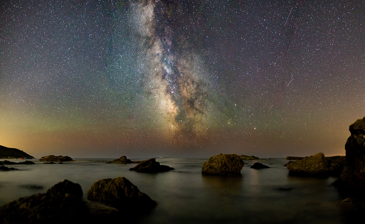 Rocks in water at night with galaxy sky