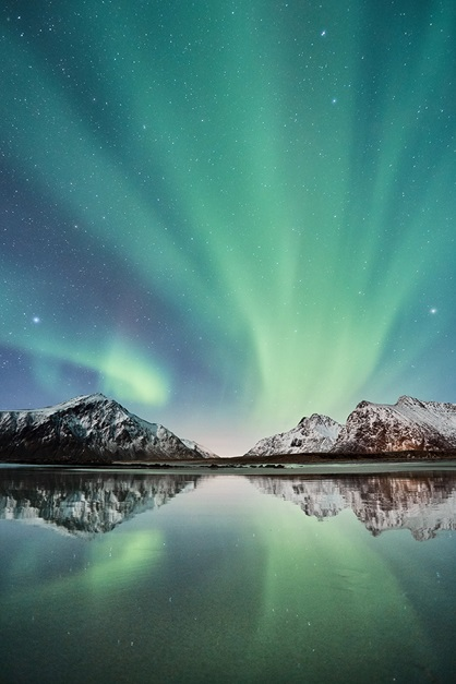 Aurora borealis with snow covered mountains and reflection in water