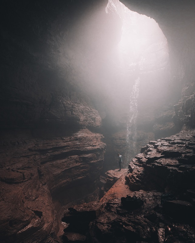 Person standing in deep cave with sunlight from above
