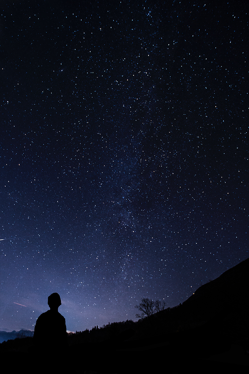 Person silhouetted looking up at stars