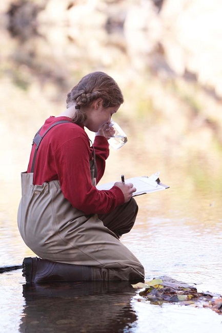 Young woman recording data from water sample in creek