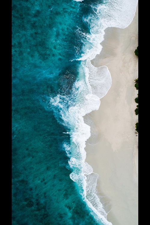 Vertical image of waves crashing on a sandy beach