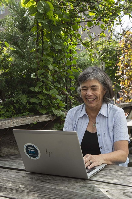 woman smiling while typing on computer outside on picnic table
