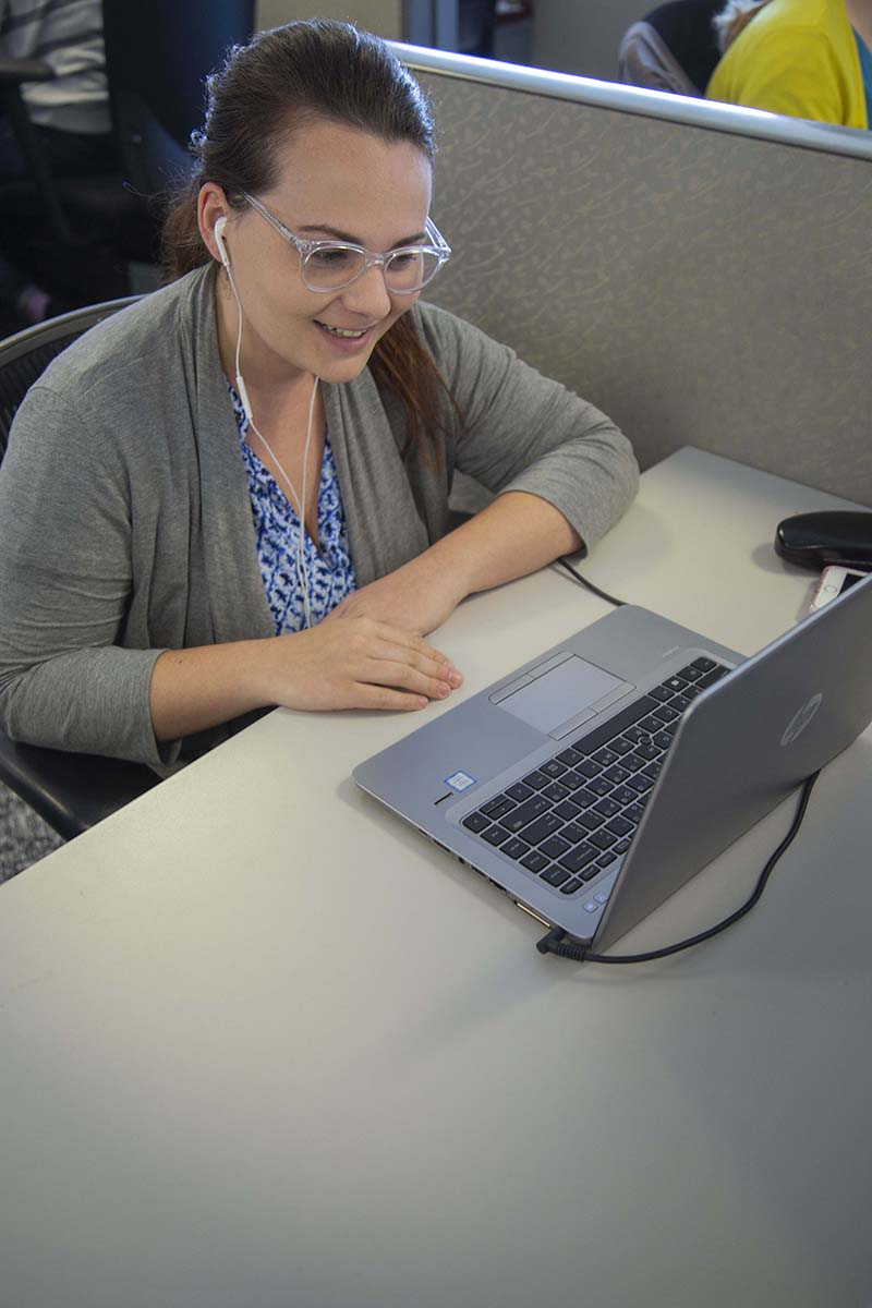 Woman smiling at computer in her office cubicle