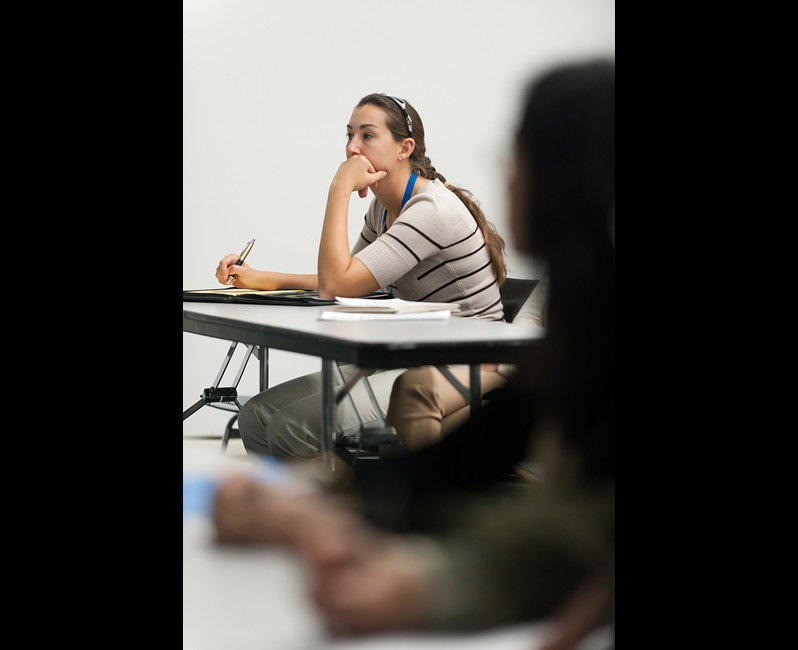Young Woman taking notes and listening in Classroom