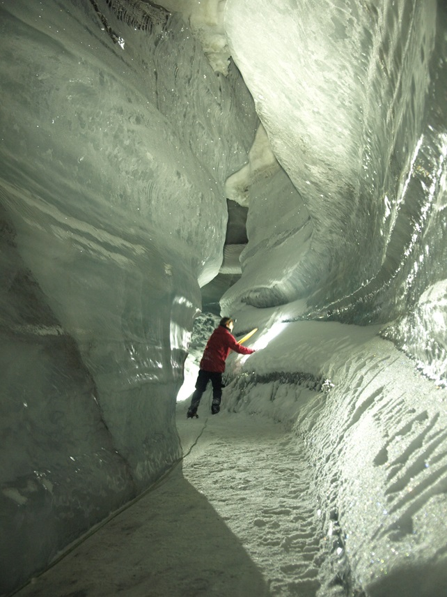 Glaciologist standing inside a glacial ice cave