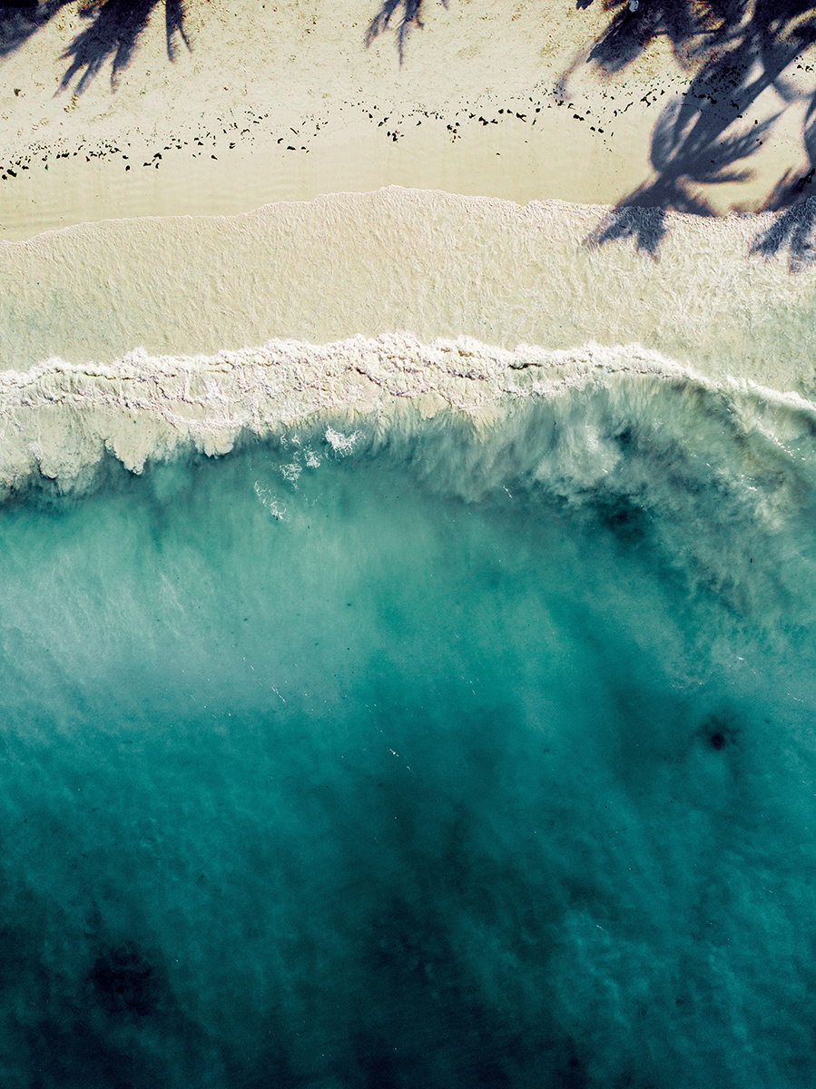 Aerial view of beach and teal ocean water